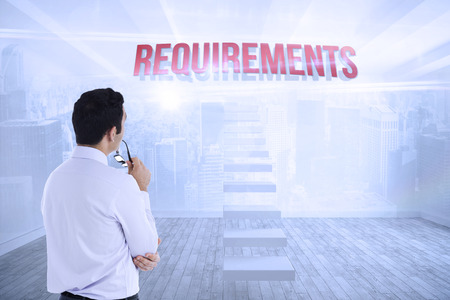 The word requirements and businessman holding glasses against city scene in a room Stock Photo