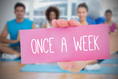 once: Woman holding pink card saying once a week against yoga class in gym