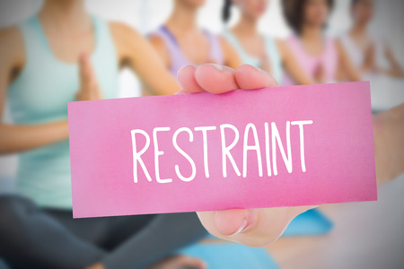 restraint: Woman holding pink card saying restraint against fitness class in gym Stock Photo
