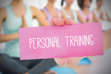 Woman holding pink card saying personal training against yoga class in gym