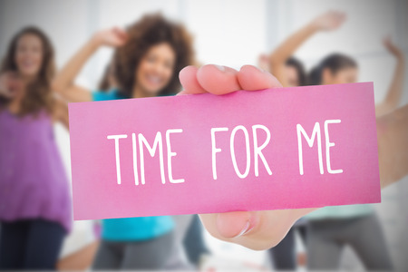 ejercicio aer�bico: Mujer que sostiene la tarjeta rosa vez para m� en contra de la clase de baile en el gimnasio diciendo Foto de archivo