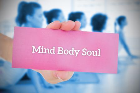 mind body soul: Donna di carta rosa dicendo anima corpo mente contro la classe di yoga in palestra Archivio Fotografico