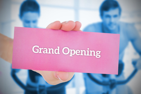 Woman holding pink card saying grand opening against spinning class in gym photo