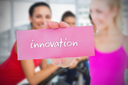 Fit blonde holding card saying innovation against spinning class in gym photo