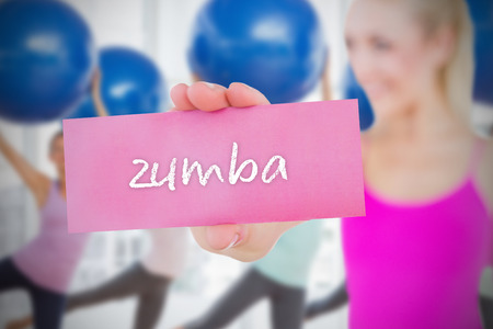 Fit blonde holding card saying zumba against fitness class in gym photo