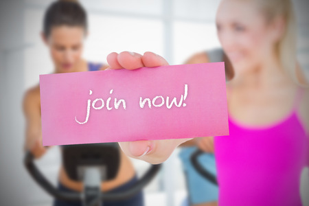 Fit blonde holding card saying join now against spinning class in gym photo