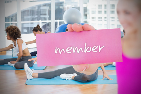 Fit blonde holding card saying member against yoga class in gym photo