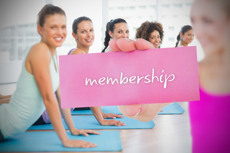 Fit blonde holding card saying membership against yoga class in gym photo