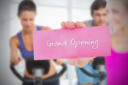 Fit blonde holding card saying grand opening against spinning class in gym photo