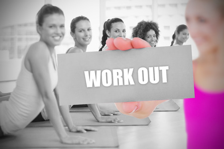 Fit blonde holding card saying work out against yoga class in gym  photo