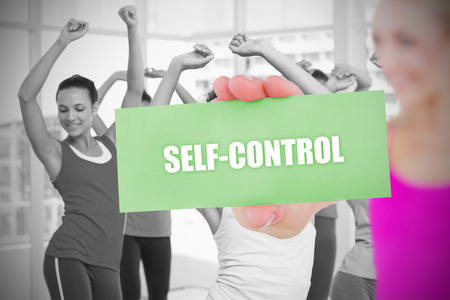 selfcontrol: Fit blonde holding card saying self control against dance class in gym  Stock Photo