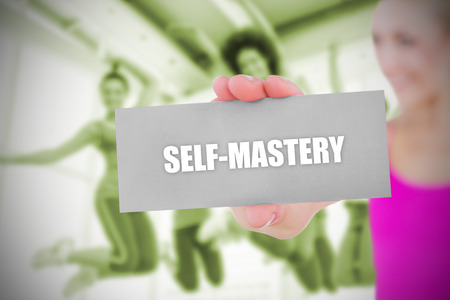 mastery: Fit blonde holding card saying self mastery against dance class in gym