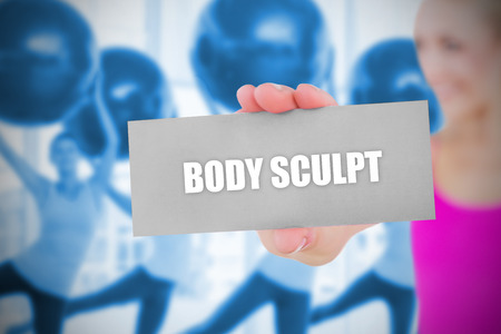 sculpt: Fit blonde holding card saying body sculpt against fitness class in gym