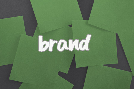 untidy text: The word brand against green paper strewn over black