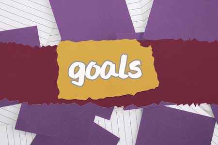 untidy text: The word goals against purple paper strewn over notepad