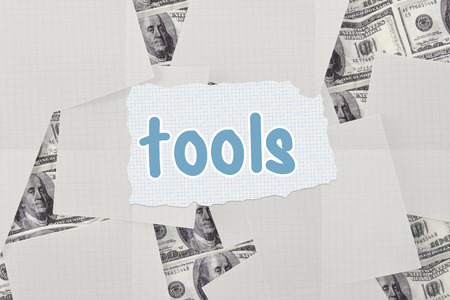 untidy text: The word tools against white paper strewn over dollar bills Stock Photo