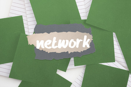 untidy text: The word network against green paper strewn over notepad