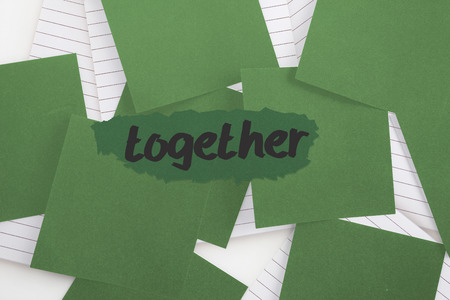 untidy text: The word together against green paper strewn over notepad