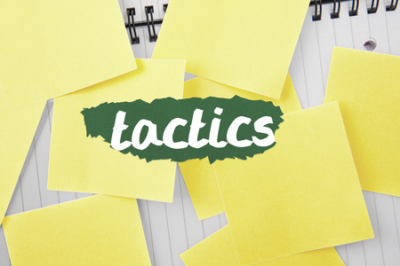 untidy text: The word tactics against sticky notes strewn over notepad Stock Photo