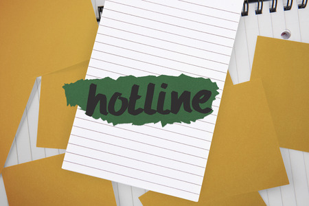 untidy text: The word hotline against yellow paper strewn over notepad