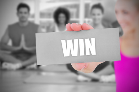 Fit blonde holding card saying win against yoga class in gym photo