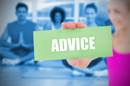 Fit blonde holding card saying advice against yoga class in gym photo