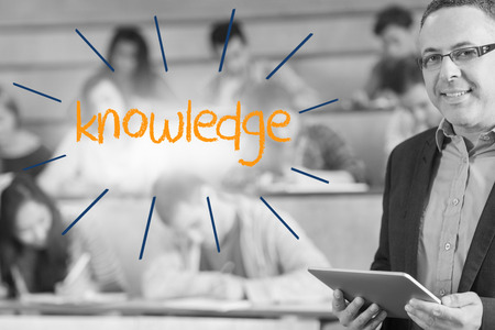 The word knowledge against lecturer standing in front of his class in lecture hall photo
