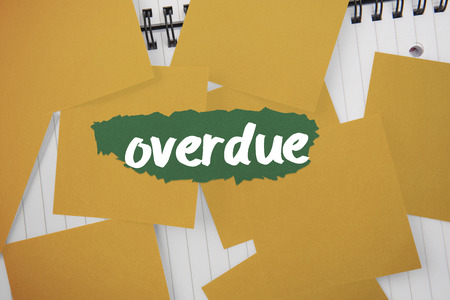 overdue: The word overdue against yellow paper strewn over notepad Stock Photo