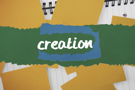 untidy text: The word creation against yellow paper strewn over notepad