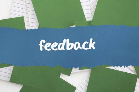 untidy text: The word feedback against green paper strewn over notepad
