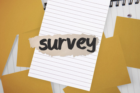 untidy text: The word survey against yellow paper strewn over notepad