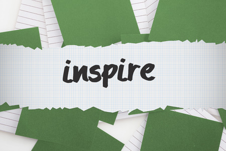untidy text: The word inspire against green paper strewn over notepad