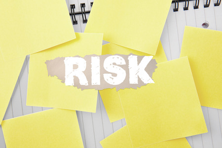 untidy text: The word risk against sticky notes strewn over notepad