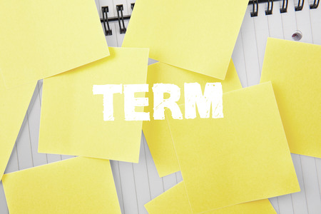 untidy text: The word term against sticky notes strewn over notepad Stock Photo