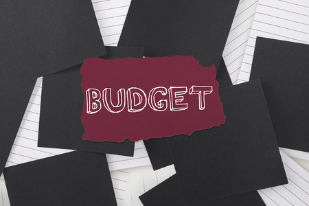 untidy text: The word budget against black paper strewn over notepad