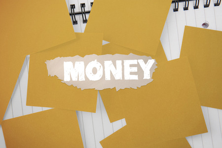 untidy text: The word money against yellow paper strewn over notepad