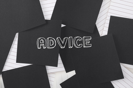 untidy text: The word advice against black paper strewn over notepad Stock Photo
