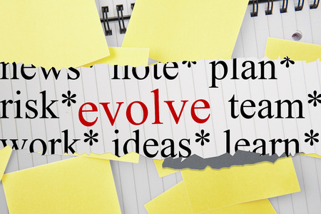 evolve: The word evolve against sticky notes strewn over notepad
