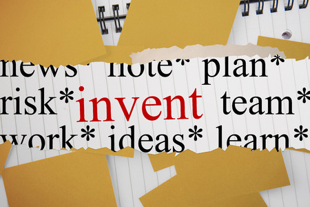 untidy text: The word invent against yellow paper strewn over notepad