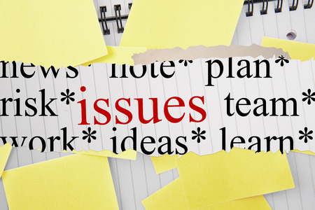 untidy text: The word issues against sticky notes strewn over notepad