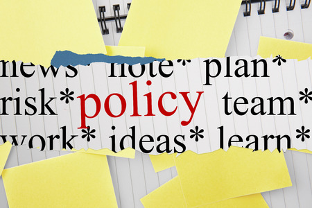 untidy text: The word policy against sticky notes strewn over notepad Stock Photo