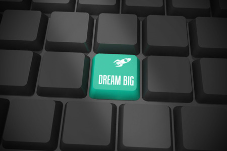 The word dream big and rocket ship on black keyboard with green key photo