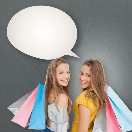 Two young women with shopping bags against speech bubble photo