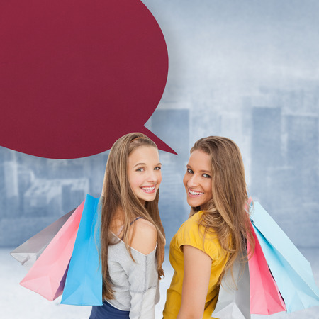 Two young women with shopping bags with speech bubble against city scene in a room photo