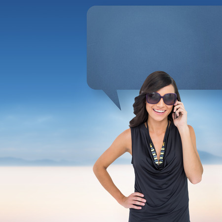 Happy brunette phoning with speech bubble against serene landscape photo