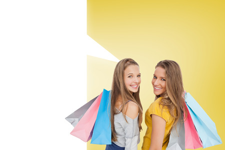 Two young women with shopping bags with speech bubble against yellow vignette photo