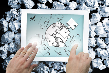 Composite image of hand touching tablet showing jigsaw and earth doodle photo
