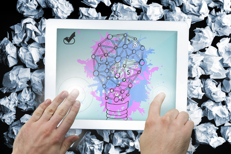 Composite image of hand touching tablet showing light bulb on paint splashes photo