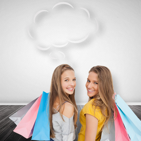 Two young women with shopping bags with speech bubble against thought bubble photo