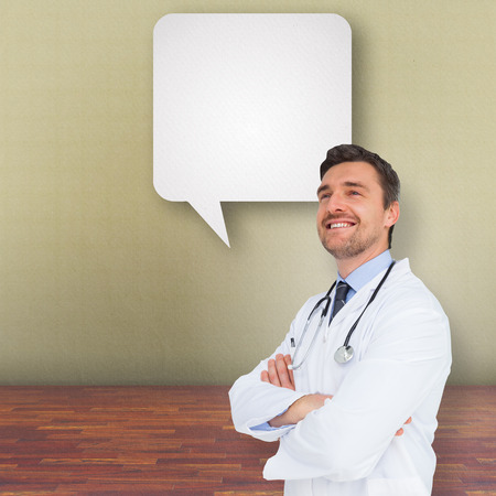Handsome young doctor with arms crossed against speech bubble photo